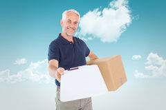 Composite image of happy delivery man holding cardboard box and clipboard Royalty Free Stock Photography