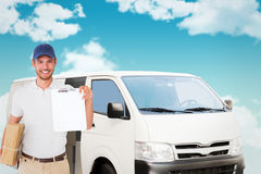 Composite image of happy delivery man holding cardboard box and clipboard Stock Photo