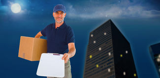 Composite image of happy delivery man holding cardboard box and clipboard Royalty Free Stock Photos