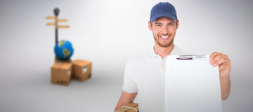 Composite image of happy delivery man holding cardboard box and clipboard. Happy delivery man holding cardboard box and clipboard against grey background Stock Photo