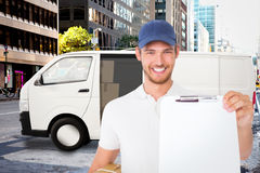 Composite image of happy delivery man holding cardboard box and clipboard Stock Images