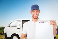 Composite image of happy delivery man holding cardboard box and clipboard Royalty Free Stock Images