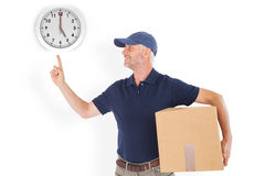 Composite image of happy delivery man holding cardboard box and pointing up Stock Photos