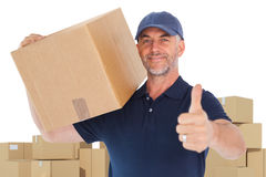 Composite image of happy delivery man holding cardboard box showing thumbs up Royalty Free Stock Images