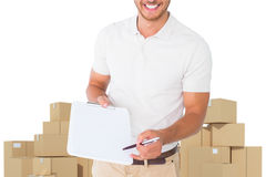 Composite image of happy delivery man holding clipboard stock image