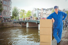 Composite image of happy delivery man leaning on pile of cardboard boxes Stock Photo