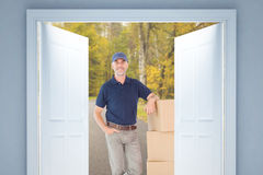 Composite image of happy delivery man leaning on pile of cardboard boxes Royalty Free Stock Photos