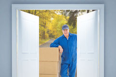 Composite image of happy delivery man leaning on pile of cardboard boxes Stock Photos