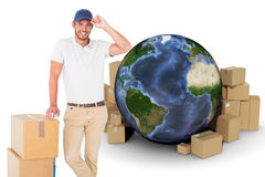Composite image of happy delivery man leaning on trolley of boxes royalty free stock images