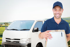Composite image of happy delivery man with package and clipboard Royalty Free Stock Image