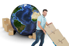 Composite image of happy delivery man pushing trolley of boxes Royalty Free Stock Image