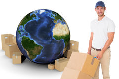 Composite image of happy delivery man pushing trolley of boxes Royalty Free Stock Images