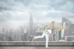 Composite image of happy delivery man running while holding parcel Royalty Free Stock Photos