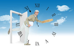 Composite image of happy delivery man running while holding parcel. Happy delivery man running while holding parcel against clock counting down to midnight Stock Image