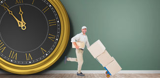 Composite image of happy delivery man with trolley of boxes running Stock Photos