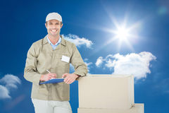Composite image of happy delivery man writing on clipboard by cardboard boxes Royalty Free Stock Image