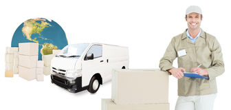 Composite image of happy delivery man writing on clipboard by cardboard boxes Royalty Free Stock Photography