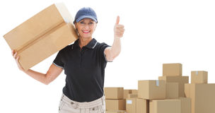 Composite image of happy delivery woman holding cardboard box Stock Photo