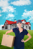 Composite image of happy delivery woman holding cardboard box. Happy delivery woman holding cardboard box  against blue sky Royalty Free Stock Photography