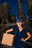 Composite image of happy delivery woman holding cardboard box Stock Photos