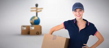 Composite image of happy delivery woman holding cardboard box. Happy delivery woman holding cardboard box against grey background Stock Images