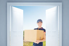 Composite image of happy delivery woman holding cardboard box Royalty Free Stock Images
