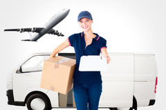 Composite image of happy delivery woman holding cardboard box and clipboard Stock Photography