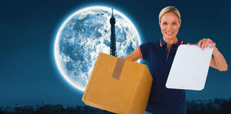 Composite image of happy delivery woman holding cardboard box and clipboard Royalty Free Stock Photography