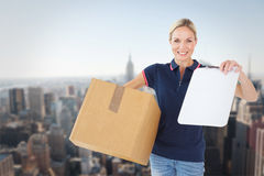 Composite image of happy delivery woman holding cardboard box and clipboard Stock Image