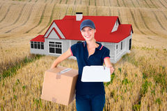 Composite image of happy delivery woman holding cardboard box and clipboard Royalty Free Stock Photo