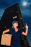 Composite image of happy delivery woman holding cardboard box and pointing up Stock Images