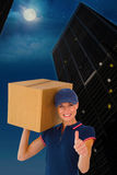 Composite image of happy delivery woman holding cardboard box showing thumbs up Royalty Free Stock Photography