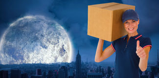 Composite image of happy delivery woman holding cardboard box showing thumbs up Stock Photos