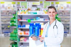 Composite image of happy doctor holding tablet pc. Happy doctor holding tablet pc against close up of shelves of drugs Stock Images
