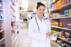 Composite image of happy doctor using her tablet pc. Happy doctor using her tablet pc against close up of shelves of drugs Stock Images
