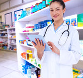 Composite image of happy doctor using her tablet pc. Happy doctor using her tablet pc against close up of shelves of drugs Stock Photography