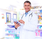 Composite image of happy doctor using tablet pc Stock Photography