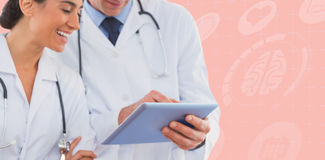 Composite image of happy doctors looking at clipboard stock photos
