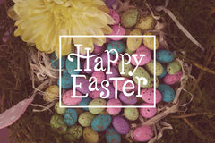 Composite image of happy easter. Happy easter against colorful easter eggs in wicker basket with flower royalty free stock photo