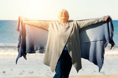 Composite image of happy elder woman raising her arms up. Happy elder woman raising her arms up  against a picture of a beach Stock Photo