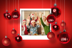 Composite image of happy extended family in santa hat cheering at camera Stock Images