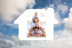 Composite image of happy family having fun on a bed Stock Photography