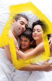 Composite image of happy family lying in bed Stock Photo