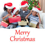 Composite image of happy family playing with christmas presents Stock Images