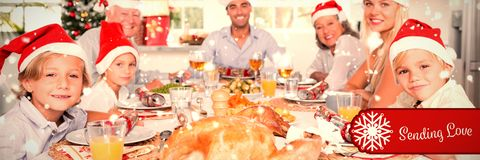 Composite image of happy family wearing santa hats around the dinner table stock photo