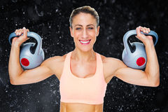 Composite image of happy female crossfitter lifting kettlebells looking at camera Royalty Free Stock Photo