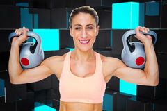 Composite image of happy female crossfitter lifting kettlebells looking at camera Stock Image