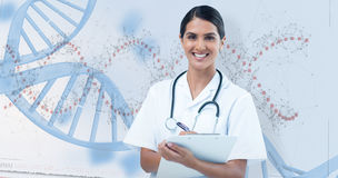 Composite image of happy female doctor writing on clipboard Stock Photos