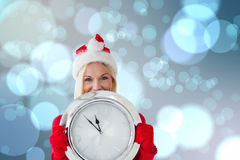 Composite image of happy festive blonde with clock Royalty Free Stock Photo
