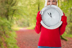 Composite image of happy festive blonde with clock Stock Photos